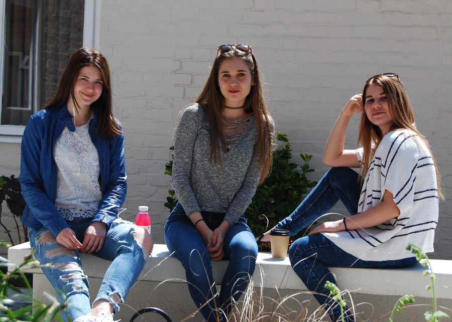 3 teenage girls sitting on the bench in sunshine