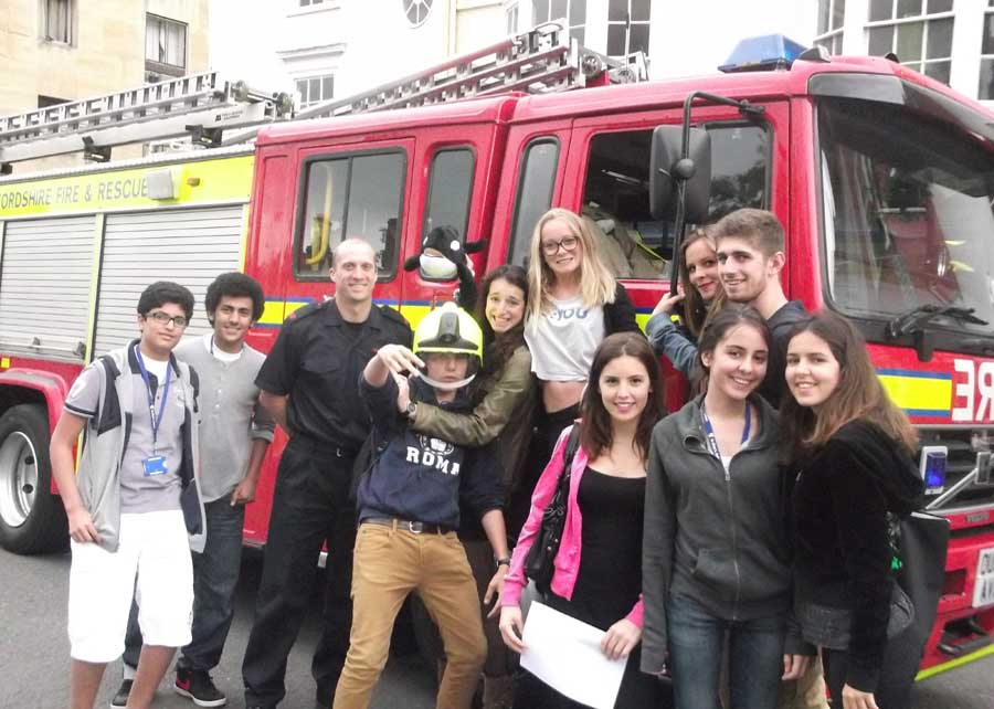 students smiling in front of a fire engine with fire fighter